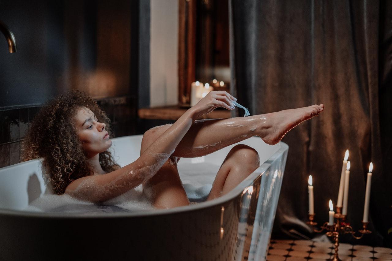 Frau rasiert sich die Beine